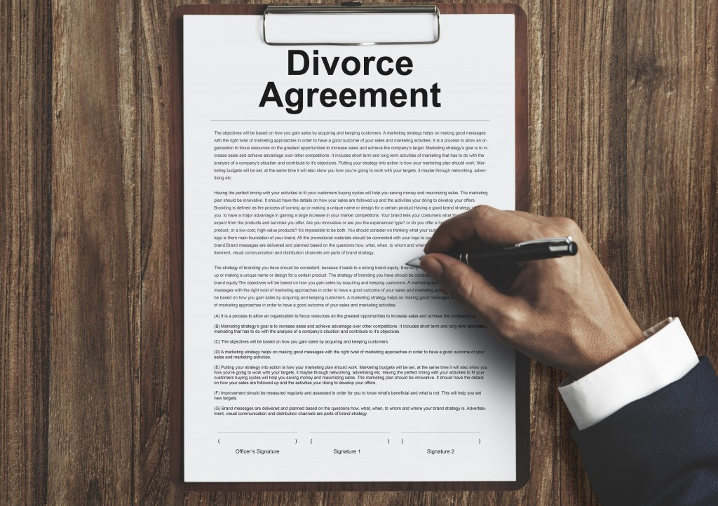 man signing divorce agreement