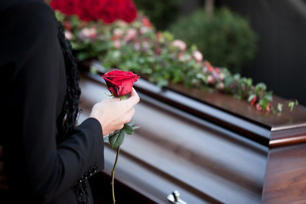 Woman holding rose in a funeral